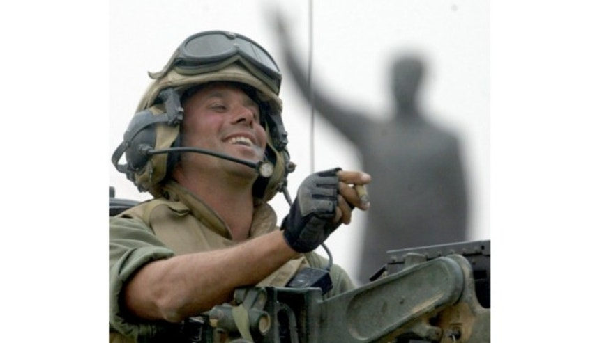 FILE: April 9, 2003: Staff Sgt. Nick Popaditch of the 3rd Battalion, 4th Marines Regiment, smokes a cigar while standing on top of his tank, as he arrives at a main crossroad in downtown Baghdad. A statue of then Iraqi President Saddam Hussein is in the background.