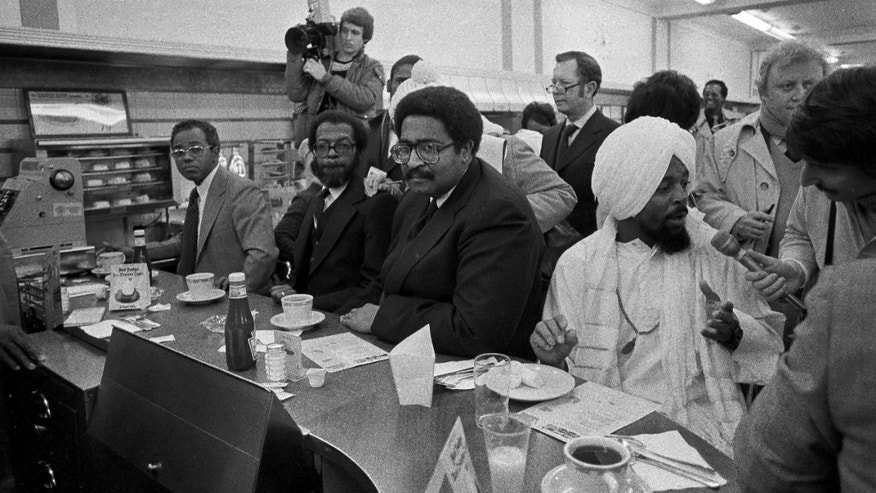 FILE - In a  Feb. 1, 1980 file photo, former North Carolina A & T students, left to right, Joseph McNeill, David Richmond, Franklin McCain and Jibreel Khazan, sit at the F.W. Woolworth lunch counter in Greensboro, N.C., as they celebrate the 20th anniversary of their historic sit-in. The four were not served in 1960 but their action launched  the sit-in movement in more than nine states.  (AP Photo/Bob Jordan, File)