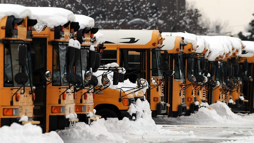 Indianapolis Public School buses sit covered in snow at a depot, Thursday, Jan. 9, 2014 in Indianapolis.  Dozens of school districts across central and northern Indiana continue to be closed as roads and sidewalks remain clogged with snow. Friday makes a full week of missed school days in many schools districts following Sunday's deep snowfall in many areas followed by the subzero temperatures that swept across the state early in the week. (AP Photo/The Indianapolis Star, Brent Drinkut )  NO SALES