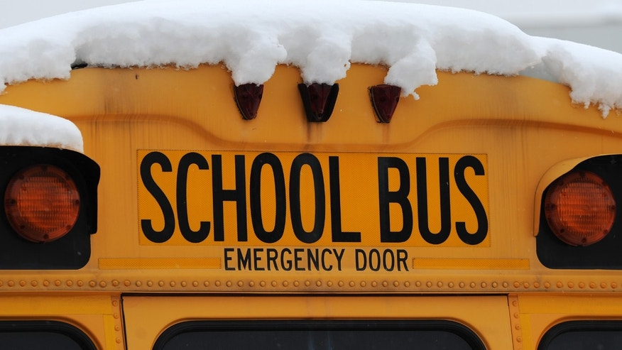 An Indianapolis Public School bus sits covered in snow at a depot, Thursday, Jan. 9, 2014 in Indianapolis.  Dozens of school districts across central and northern Indiana continue to be closed as roads and sidewalks remain clogged with snow. Friday makes a full week of missed school days in many schools districts following Sunday's deep snowfall in many areas followed by the subzero temperatures that swept across the state early in the week. (AP Photo/The Indianapolis Star, Brent Drinkut )  NO SALES