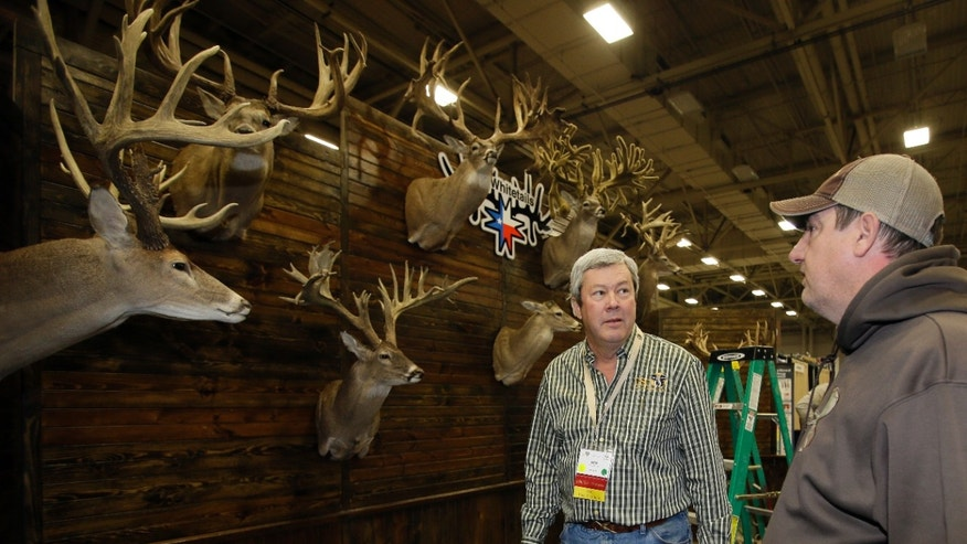 Dallas Safari Club executive director Ben Carter talks with Mike Woods of 4JM White Tails Hunting in the Dallas Exhibit Hall as set up continues for the clubs weekend show, Wednesday, Jan. 8, 2014, in Dallas. The FBI is investigating death threats made against members of the Dallas Safari Club, which intends to auction off a rare permit to hunt an endangered black rhino, an FBI spokeswoman said Wednesday. (AP Photo/Tony Gutierrez)