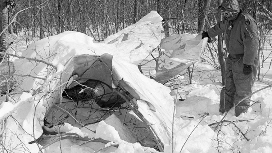 This Jan. 15, 1964 file photo shows a sentry inspecting debris from a Strategic Air Command B-52 bomber that was carrying two unarmed nuclear bombs before it crashed near Cumberland, Md.