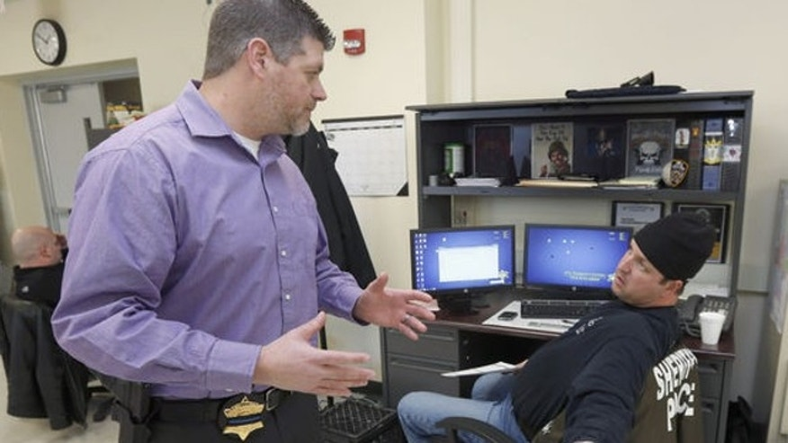 Jan. 8, 2014: John Blair, left, executive director of the Cook County Sheriff's Office Intelligence Center, consults with Officer John Slepski about a firearms background check Slepski is performing at the center in Chicago.