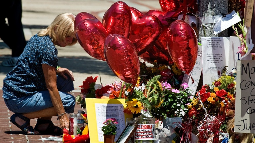 August 9: Cathy Thomas puts a candle blown over in the wind upright at the memorial that supporters have created near the spot where her son Kelly Thomas and police officers had their altercation in Fullerton, California. Kelly Thomas died at UCI Medical Center in Orange, five days after being involved in the physical confrontation with police.