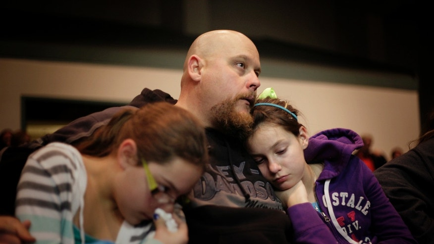 Troy Tucker, center of Roswell, N.M., holds his daughters Emily Tucker, left age 10, and Hannah Tucker, right age 12, during a community prayer vigil for the victims of the Berrendo Middle School shooting in Roswell, N.M., Tuesday Jan. 14, 2014.  Officials and witnesses say a 12-year-old boy drew a shotgun from a band-instrument case and shot two classmates at his Roswell school before a teacher talked him into dropping the weapon. A boy was critically injured and a girl was in satisfactory condition following the shooting yesterday morning at Berrendo Middle School. (AP Photo/Albuquerque Journal, Pat Vasquez-Cunningham)