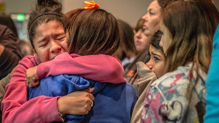 Thirteen year old Kimberly Macias cries as she sees schoolmates at a vigil for the victims, Tuesday, Jan. 14, 2014 in Roswell, N.M. A 12-year-old New Mexico boy drew a shotgun from a band-instrument case and shot and wounded two classmates at his middle school Tuesday morning before a teacher talked him into dropping the weapon and he was taken into custody, officials and witnesses said. (AP Photo/The Albuquerque Journal, Roberto Rosales)  THE SANTA FE NEW MEXICAN OUT&#x3b;  MANDATORY CREDIT: ROBERTO ROSALES/THE ALBUQUERQUE JOURNAL