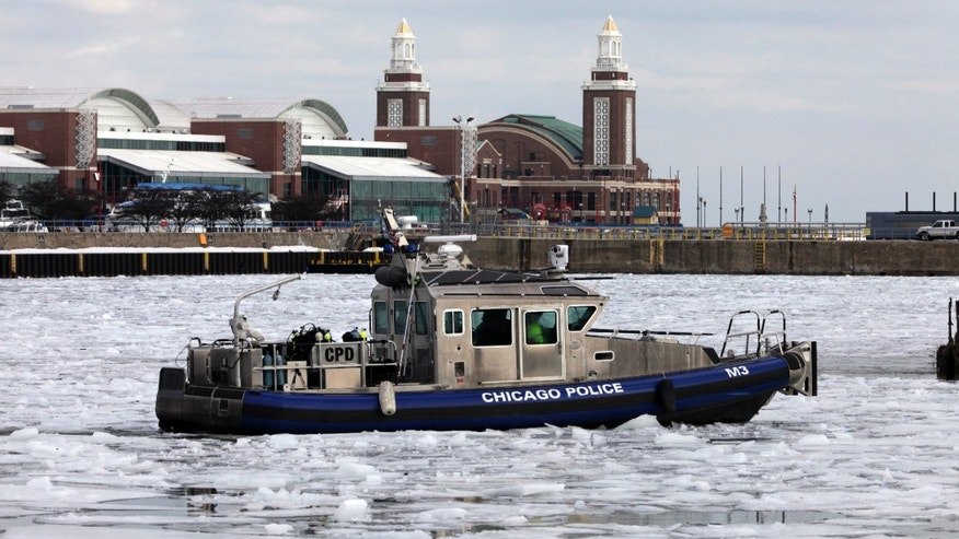 A search crew of the Chicago Police Department's marine unit returns to the marine safety station in Chicago after their search for 21-year-old Lauren Li. Police have said Li and two friends fell into the icy river earlier this week after Ken Hoang, 26, jumped over a fence in downtown Chicago to retrieve a cellphone he'd dropped in the water. Li and Quoc-Viet Phan Hoang, 23, both University of Minnesota students, tried to help, but fell in after their friend. Ken Hoang, a former University of Minnesota student from St. Paul, Minn., was pronounced dead after he was pulled from the river Monday. Li's body was pulled from the river on Wednesday. (AP Photo/Kiichiro Sato)