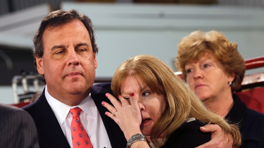 Amy Peters, of Manahawkin, N.J., wipes a tear as she is hugged by New Jersey Gov. Chris Christie Thursday, Jan. 16, 2014, in Manahawkin, N.J., as he meets with homeowners who lost their homes last year to Superstorm Sandy. Christie spoke to Superstorm Sandy victims one week after the meeting was hastily canceled because of a scandal over traffic jams that appear to have been manufactured by his aides. Christie and Community Affairs Commissioner Richard Constable III announced a Sandy housing recovery milestone Thursday as the governor seeks to put the traffic scandal behind him. (AP Photo/Mel Evans)