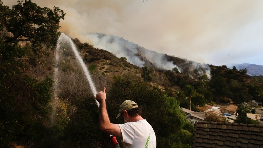 Mark Davis gives a thumbs-up toward a helicopter as he sprays water around his property, Thursday, Jan. 16, 2014, in Azusa, Calif. A wildfire burned out of control near homes in the dangerously dry foothills of the San Gabriel Mountains early Thursday, fanned by gusty Santa Ana winds that spit embers into neighborhoods in the city below, igniting trees. Evacuations were ordered for houses at the edge of the fire. (AP Photo/Jae C. Hong)