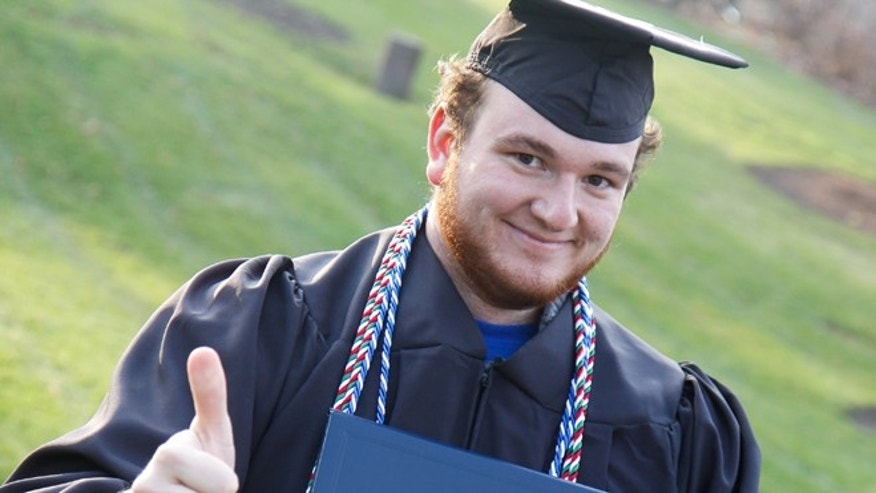 This 2013 photo shows Alex Benda, 22, anticipating his graduation from the University of Michigan-Flint. He's selling ad space on his graduation cap in an effort to pay off his college debt by May.
