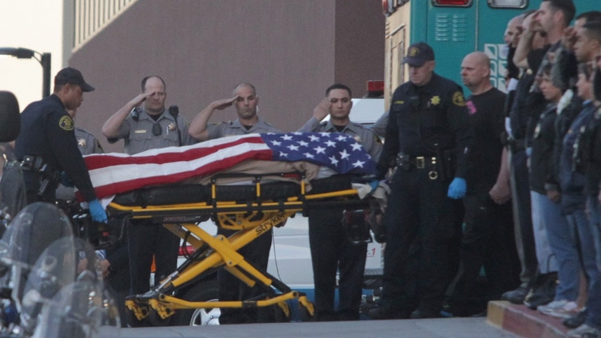 Jan. 21, 2014: Law enforcement officers salute as the body of a Bay Area Rapid Transit police officer draped with the American flag is loaded into an Alameda County Sheriff's Coroner vehicle at Eden Medical Center in Castro Valley, Calif.