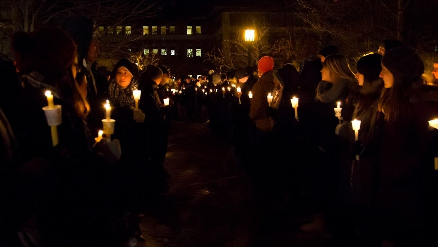 A path is lit for members of the Purdue All-American Marching Band during a vigil for a teaching assistant who was fatally shot on campus at Purdue University, on Tuesday, Jan. 21, 2014, in West Lafayette, Ind. The victim was identified as Andrew Boldt, 21, a senior in electrical engineering from Wisconsin who lived on campus, according to Purdue. Another student, Cody Cousins, was arrested on a preliminary charge of murder, athourities said. (AP Photo/The Journal & Courier, Michael Heinz) MANDATORY CREDIT; NO SALES