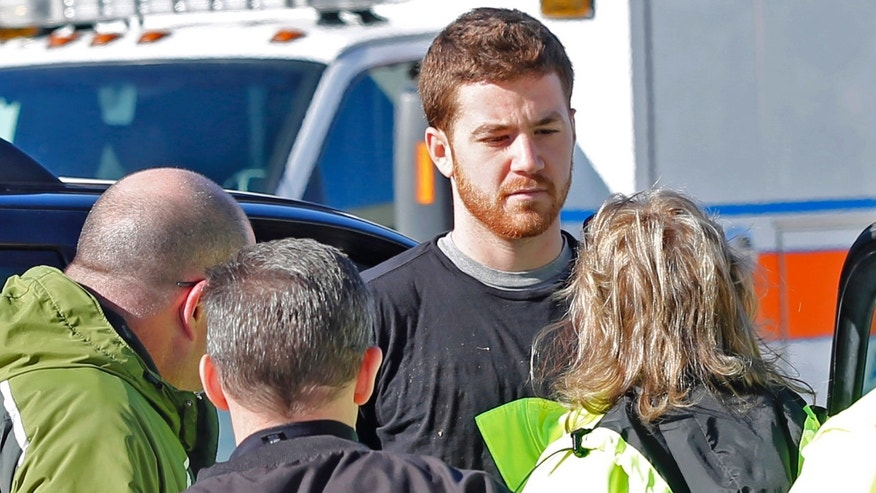 EMS personnel speak with an Cody Cousins, 23, who was detained after a shooting inside the Electrical Engineering building on the campus of Purdue University in West Lafayette, Ind. Cousins, of Warsaw, Ind., is being held in the Tippecanoe County Jail on a preliminary charge of murder, accused of shooting 21-year-old Andrew Boldt of West Bend, Wis. (AP Photo/The Journal & Courier, John Terhune) MANDATORY CREDIT; NO SALES