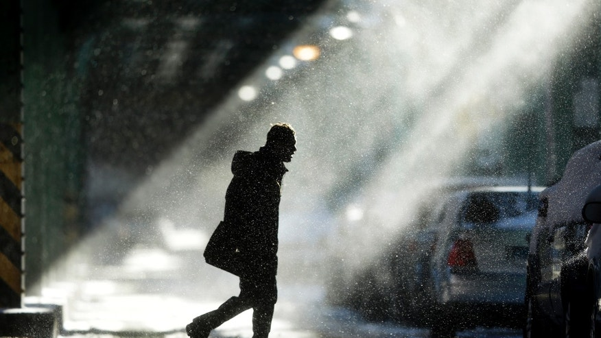 The sun illuminates windblown snow as a man walks under elevated train tracks, Wednesday, Jan. 22, 2014, in Philadelphia.  A winter storm stretched from Kentucky to New England and hit hardest along the heavily populated Interstate 95 corridor between Philadelphia and Boston.   (AP Photo/Matt Rourke)