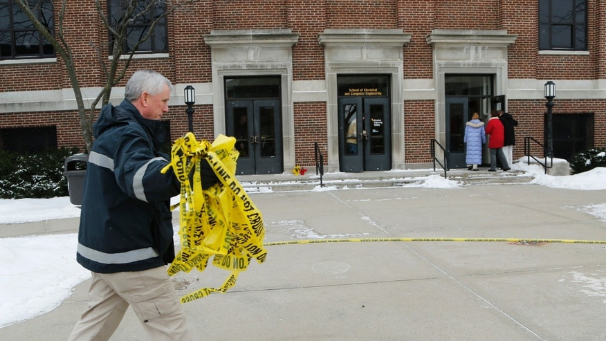 Kevin Luse of Purdue University Fire Department collects police tape as the Electrical Engineering building is opened, Wednesday, January 22, 2014, on the campus of Purdue University, in West Lafayette, Ind. The building had been closed since engineering student Andrew Boldt was shot and killed Tuesday. Cody Cousins, a student, has been charged in the shooting.  (AP Photo/Journal & Courier, John Terhune)