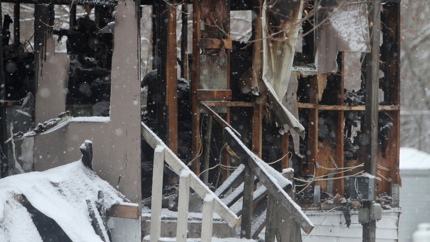 In this Jan. 20, 2014 photo, snow falls on the burned out shell of a mobile home in Penfield, N.Y. Firefighters are calling eight-year-old Tyler Doohan a hero after his actions alerted and saved six of the nine people living in the 14-foot-by-60-foot trailer after fire broke out in the early morning hours of Monday. Doohan died while trying to save his disabled grandfather from the flames. His grandfather and an uncle perished. (AP Photo/Rochester Democrat and Chronicle, Tina McIntyre-Yee)