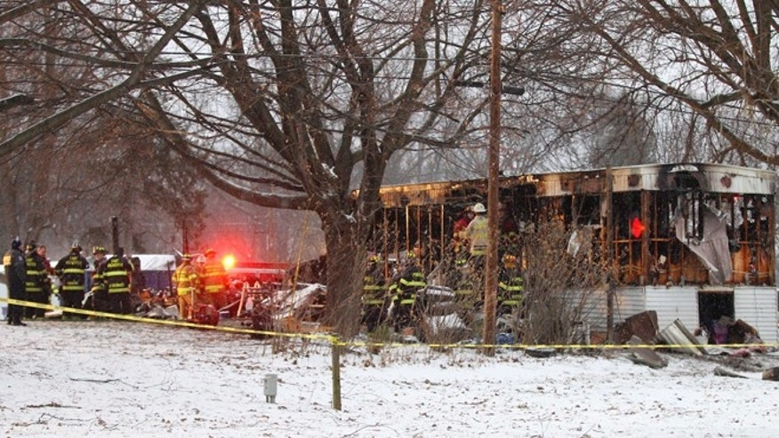 In this Jan. 20, 2014 photo, firefighters investigate a fatal fire in a mobile home in Penfield, N.Y. Eight-year-old Tyler Doohan died in the flames while trying to save his handicapped grandfather. Doohans grandfather and uncle died along with him but fire fighters are calling him a hero. Six people got out of the burning trailer alive because he woke them up. (AP Photo/Rochester Democrat and Chronicle, Jamie Germano) MAGS OUT. NO SALES.