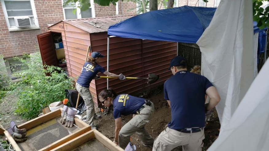 """FILE - In this June 18, 2013 file photo, FBI agents search the backyard of a house once occupied by James """"Jimmy the Gent"""" Burke in New York. Burke masterminded a $5.8 million robbery from Lufthansa Airlines in 1978. Vincent Asaro, a mob associate of Burke's, was indicted, Thursday, Jan. 23, 2014 for participating in the armed robbery at Kennedy Airport. (AP Photo/Kathy Willens, File)"""