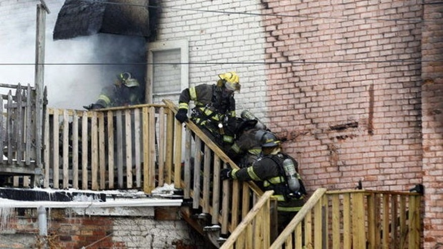 January 26, 2014: Toledo firefighters rush a fellow firefighter down the stairs of a six-unit apartment building Sunday. Two firefighters battling the blaze at the apartment complex near downtown Toledo were killed, city officials said. (Jetta Fraser, The Blade via AP)