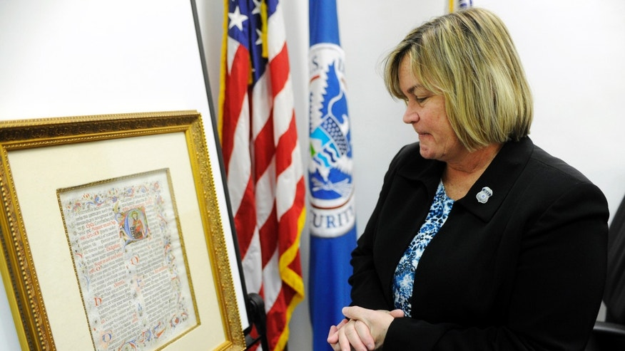 Homeland Security Special Agent in Charge Susan L McCormick looks over an Italian, religious manuscript in Tampa, Fla., Monday Jan. 27. 2014.  The manuscript  was stolen in Italy over 20 years ago. The Italian government and DHS worked together to track down the item to St. Petersburg, Fla.     (AP Photo/The Tampa Tribune, Jay Conner)  ST. PETERSBURG OUT; LAKELAND OUT; BRADENTON OUT; MAGS OUT; LOCAL TV OUT; WTSP CH 10 OUT; WFTS CH 28 OUT; WTVT CH 13 OUT; BAYNEWS 9 OUT; THE TAMPA BAY TIMES OUT; LAKELAND LEDGER OUT; BRADENTON HERALD OUT; SARASOTA HERALD-TRIBUNE OUT; WINTER HAVEN NEWS CHIEF OUT