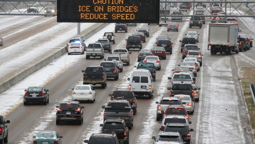 Traffic creeps along Interstate 55 in north Jackson, Miss., Tuesday, Jan. 28, 2014, as ice and snow flurries cause difficult driving conditions. A severe winter storm is expected to hit the state, bringing ice and snow to the Gulf Coast. (AP Photo/Rogelio V. Solis)