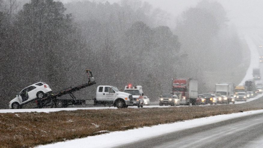 Traffic backs up as a wrecker pulls a car out of a ditch on I-65 during an unual snow Tuesday, Jan. 28, 2014, in Clanton, Ala.   A rare storm left a slippery layer of ice and snow across a region unaccustomed to dealing with the wintry threat. (AP Photo/Butch Dill)