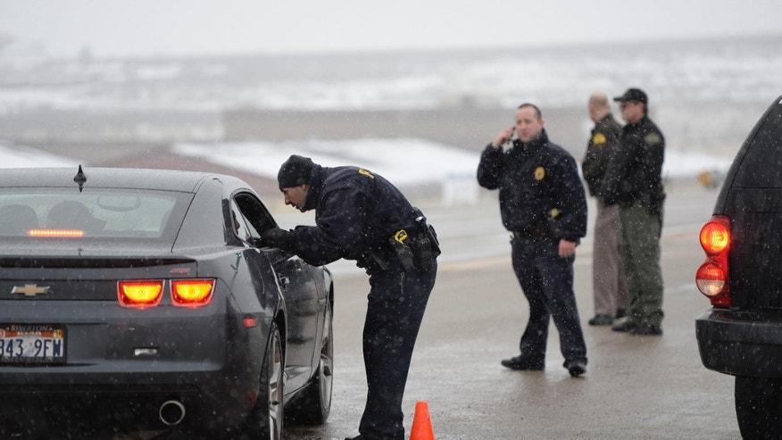 Police officers direct traffic off of SR 73 at Ranches Parkway near Eagle Mountain on Thursday, Jan. 30, 2014, following an officer shooting incident further West. (AP Photo/The Salt Lake Tribune, Francisco Kjolseth)