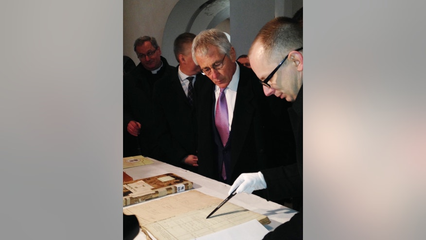 U.S. Defense Secretary Chuck Hagel, center, examines the original marriage certificate of his maternal grandmother's parents at the Dabrowka Church in Kiszkow, Poland, Friday, Jan. 31, 2014.  Dabrowka Church is located on the same site where his maternal grandmother's parents were married in 1882.  The original church burned down in the 1920's and was later rebuilt. (AP Photo/Robert Burns)
