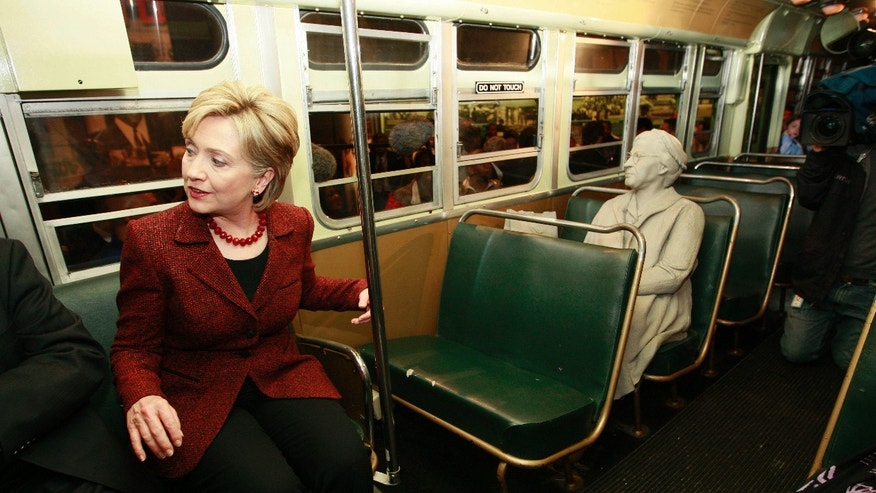 FILE - This April 4, 2008, file photo shows then-Democratic presidential hopeful Sen. Hillary Rodham Clinton, D-N.Y., sitting on a Montgomery city bus next to a likeness of Rosa Parks, right, during a visit to the National Civil Rights Museum at the Lorraine Motel on the 40th anniversary of the assassination of Rev. Martin Luther King Jr., in Memphis, Tenn.. Clinton had championed the Save America's Treasures grant program during her husband's administration. (AP Photo/Charles Dharapak)