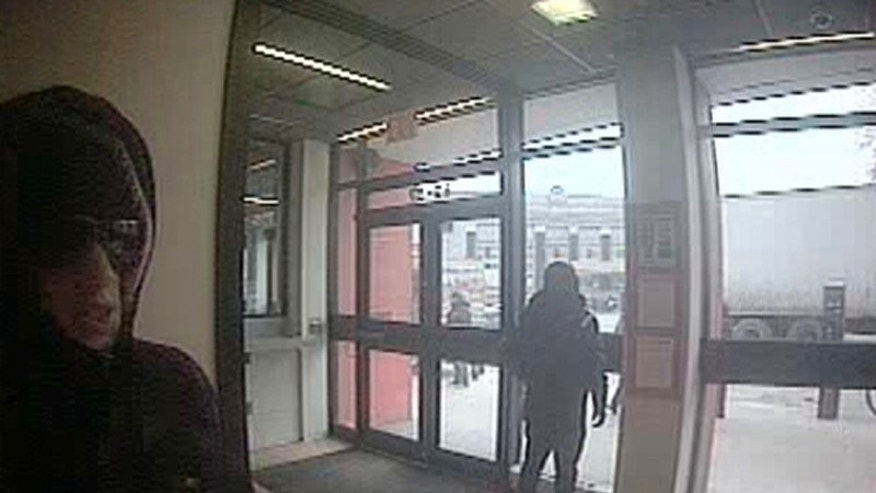 This image from surveillance video provided by the FBI Friday Jan. 31, 2014 shows suspects in the robbery of a GardaWorld armored truck guard in the lobby of the HSBC bank on Broadway in the Queens borough of New York City Friday. Federal investigators are searching for three men they say held up the armored truck guard at a Queens bank in broad daylight. Authorities didn't disclose how much was taken in the robbery that occurred inside an ATM lobby at around noon Friday at a HSBC bank branch in the Elmhurst neighborhood of Queens. (AP Photo/FBI)