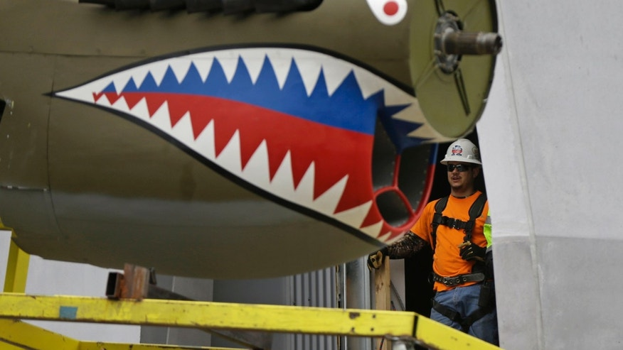 A restored P-40 Curtiss Warhawk fighter plane, one of only 32 known remaining in the world, is hoisted by crane to the second floor for permanent display at the National World War II Museum in New Orleans, Monday, Feb. 3, 2014. The plane, painted in the scheme of the famed Flying Tigers, will be displayed in the museum's new pavilion, Campaigns of Courage: European and Pacific Theaters. (AP Photo/Gerald Herbert)