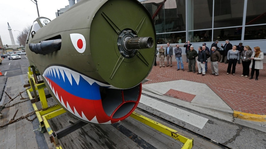 A restored P-40 Curtiss Warhawk fighter plane, one of only 32 known remaining in the world, arrives on a flatbed truck for permanent display at the National World War II Museum in New Orleans, Monday, Feb. 3, 2014. The plane, painted in the scheme of the famed Flying Tigers, will be displayed in the museum's new pavilion, Campaigns of Courage: European and Pacific Theaters. (AP Photo/Gerald Herbert)