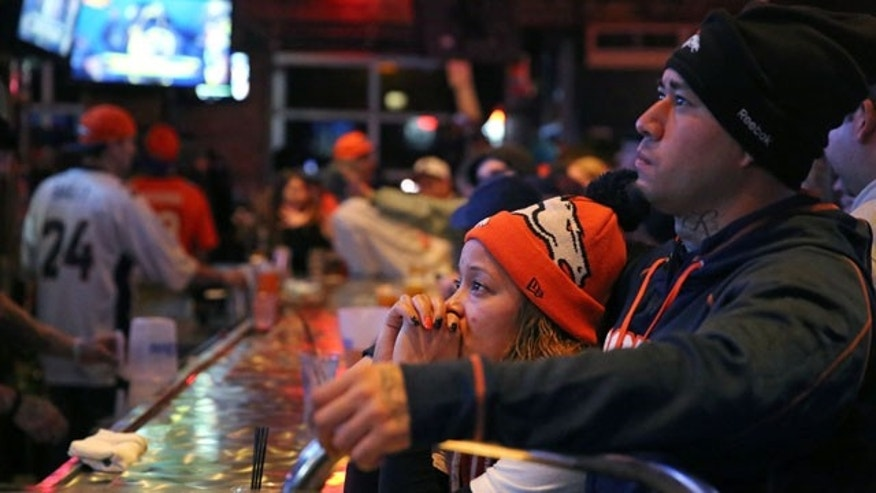 February 2, 2014: Denver Broncos fans Tatiana Bohorquez and Jorge Puerto watch their team fall further behind the Seattle Seahawks during the second half of the Super Bowl, inside Jackson's, a sports bar and grill in Denver. (AP Photo/Brennan Linsley)
