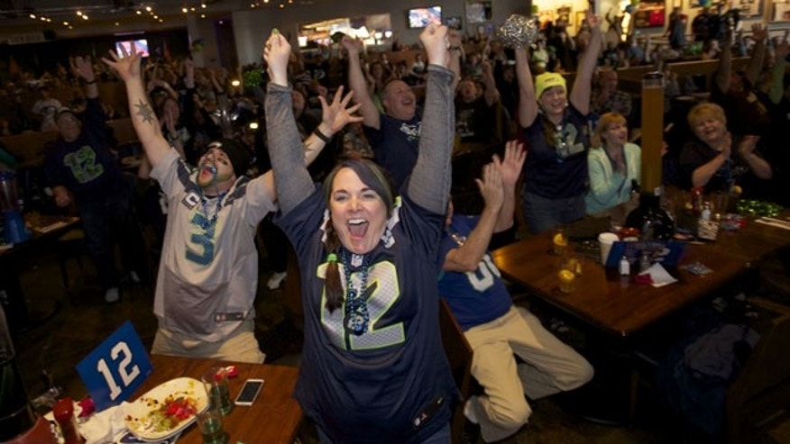 February 2, 2014: Seattle Seahawks fans Brittney Gutierrez, center, and her husband Mike Gutierrez, left, celebrate while watching Super Bowl XLVIII at Big Al's in Vancouver, Wash. Seattle defeated the Denver Broncos 43-8. (AP Photo/The Columbian, Steven Lane)