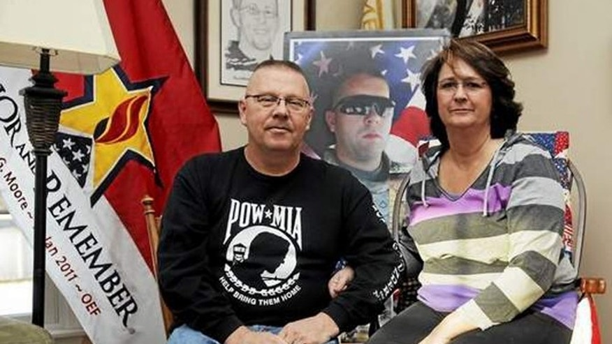 Pat and Amy Moore sit next to a collection of photos of their son, Army SPC Benjamin Moore, who was killed in Afghanistan in 2011.