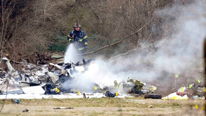 Feb. 4, 2014: A Nashville firefighter douses the wreckage from a plane crash that killed everyone on board outside the Bellevue YMCA in Nashville, Tenn.
