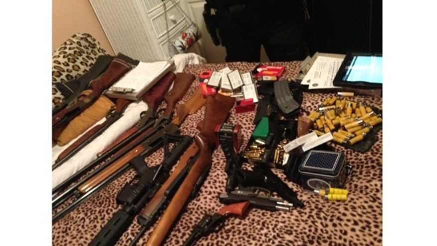 In this picture taken during the seizure on Nov. 5th by Merritt's wife, Law-enforcement officials lay out the guns on the bed for cataloging before loading them into police vehicles.