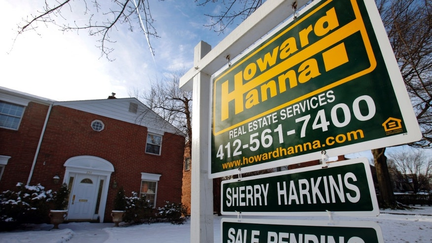 In this Thursday, Jan. 9, 2014, photo, a for sale sign is placed in front of a house in Mount Lebanon, Pa.  Freddie Mac reports on average mortgage rates for this week on Thursday, Feb. 6, 2014. (AP Photo/Gene J. Puskar)