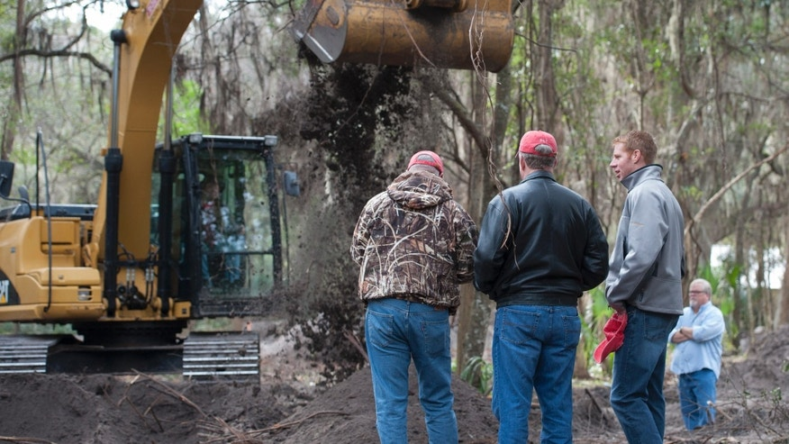 Patrick Sessions, center, and his son Jason, right, watch as Alachua County Sheriffs technicians use a back hoe Thursday, Feb. 2, 2014, in Gainesville, Fla., to dig for evidence in the 1989 disappearance of Tiffany Sessions, a University of Florida student.  The sheriffs department announced they have linked the disappearance to Paul Rowles, a serial killer who died in prison last year.   (AP Photo/Phil Sandlin)