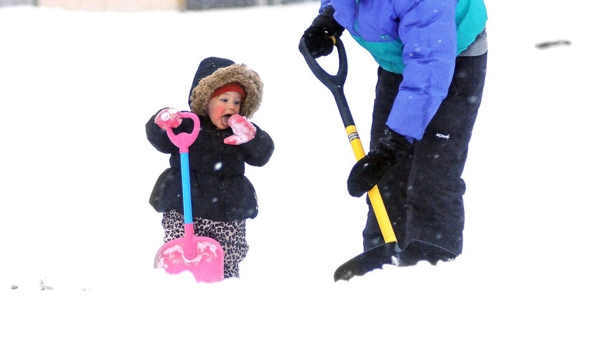Feb. 5, 2014: While Lauren Berthiaume, right, shovels her sidewalk, her 17-month-old daughter Rylie Bartusek prefers eating the snow in Worcester, Mass.