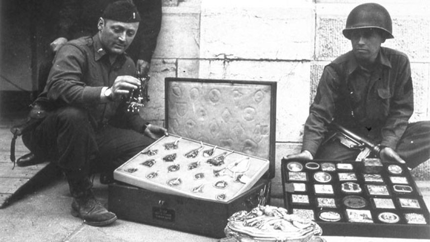 This photo provided by The Monuments Men Foundation for the Preservation of Art of Dallas, shows Monuments Man James Rorimer, left, and Sgt. Antonio Valim examining valuable art objects at Neuschwanstein Castle in Germany which were stolen from the Rothschild collection in France by the ERR and found in the castle in May of 1945. (AP)