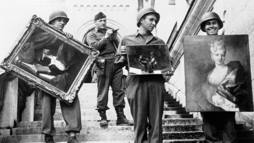FILE: May 1945: This photo provided by The Monuments Men Foundation for the Preservation of Art of Dallas, shows Monuments Man James Rorimer, with notepad, as he supervises American GI's hand-carrying paintings down the steps of the castle in Neuschwanstein, Germany.