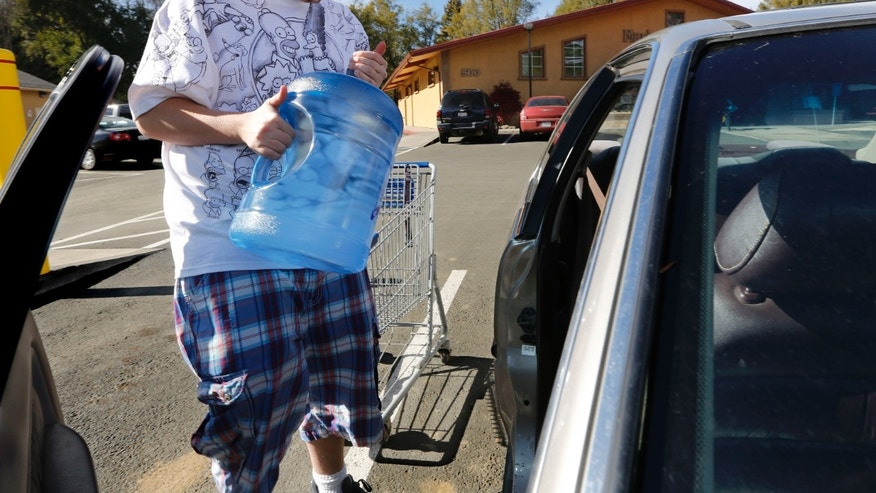 In this photo taken Tuesday, Feb. 4, 2014, Forrest Clark, 25, loads five gallon bottles of water, purchased at a local store, into his car in Willits, Calif.  With local reservoirs holding less than a 100-day supply of water, city leaders have banned lawn watering, car washing and mandated all residents to cut water use. Clark, who said he doesn't like the taste of the local water, buys 10-15 gallons of bottled water a week to help boost the family water supply.(AP Photo/Rich Pedroncelli)
