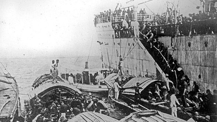 An undated photo show American troops disembarking from a ship onto small boats near Cavite, Phillipines, in 1898 or 1899.