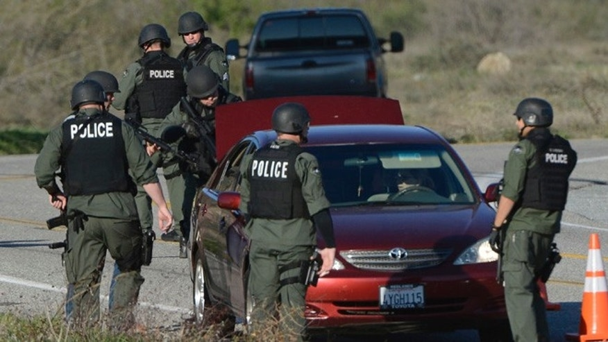 Feb. 12, 2013: SWAT officers search cars coming down highway 38 during the manhunt for former Los Angeles police officer Christopher Dorner, in Yucaipa, California.