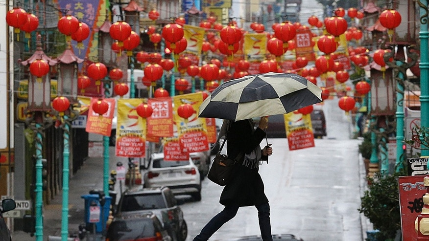 A woman carries an umbrella as she crosses the street with lanterns from Chinatown hanging behind her in San Francisco, Friday, Feb. 7, 2014. Dry California got a much needed taste of rain, but drought-watchers hope it was just a teaser for a much wetter weekend. A bigger storm expected to arrive late Friday and last through Sunday could dump as much as 2 feet of snow on the slopes of the Sierra and 6 inches of rain on San Francisco Bay Area mountains. (AP Photo/Jeff Chiu)
