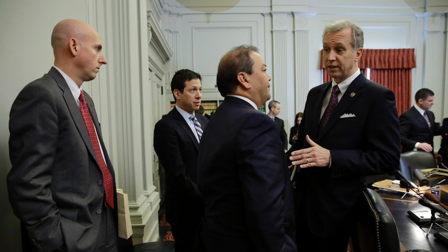 Attorney Reid Schar, left, stands with fellow attorney Anthony Barkow, second from left, as New Jersey Assemblyman John S. Wisniewski, right, D-Sayreville, N.J., co-chair of a joint bipartisan committee of members of the New Jersey Senate and Assembly, talks with Sen. Kevin J. O'Toole, R-Wayne, N.J., before a meeting at the Statehouse in Trenton, N.J., Monday, Feb. 10, 2014. More subpoenas are expected to be issued by a New Jersey legislative committee investigating a plot to create gridlock by blocking lanes near the George Washington Bridge. (AP Photo/Mel Evans)