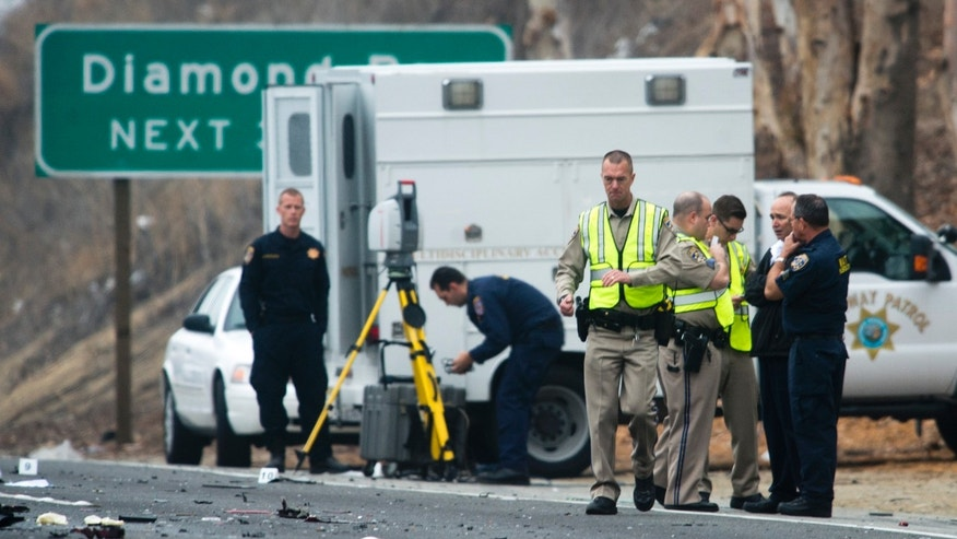 Officials investigate the scene of a multiple vehicle accident where six people were killed on the westbound Pomona Freeway in Diamond Bar, Calif., on Sunday morning, Feb. 9, 2014. Authorities say four members of a family have been killed in the wrong-way freeway crash that also took the life of two others, including the sister of a woman arrested on suspicion of drunken driving. (AP Photo/San Gabriel Valley Tribune,Watchara Phomicinda)