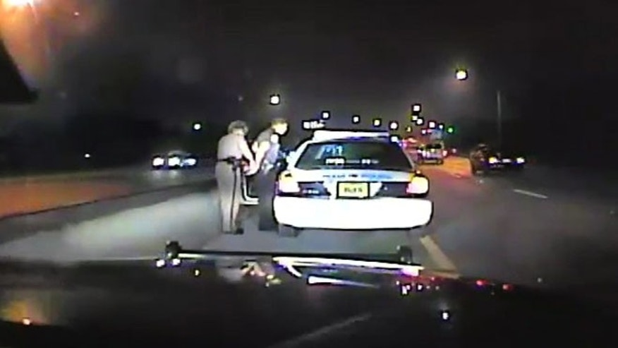 Oct. 11, 2011: In this frame grab made from a video available from the Florida Department of Highway Safety and Motor Vehicles, Florida Highway Patrol Officer Donna Jane Watts arrests Miami Police Department Officer Fausto Lopez. Watts stopped Lopez, who was traveling at 120 miles per hour, as he was heading to an off-duty job.
