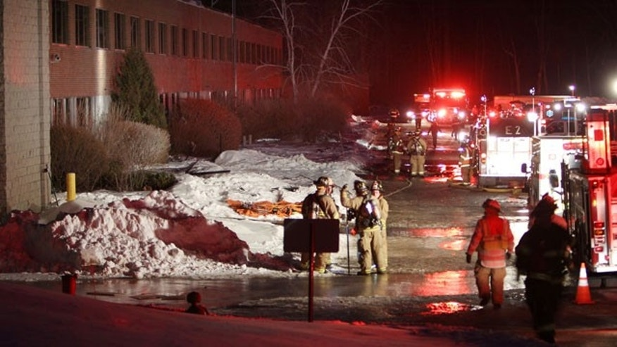February 10, 2014: Emergency crews from several towns work an area outside the New Hampshire Ball Bearing plant after an explosion in Peterborough, N.H. (AP Photo/Jim Cole)